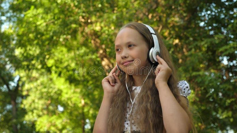 Muchacha en auriculares que escucha la música y el baile sonriente en parque del verano fotografía de archivo libre de regalías