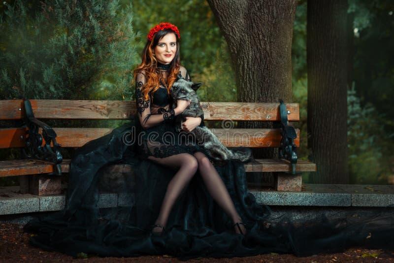 Muchacha en banco de parque con un zorro fotografía de archivo