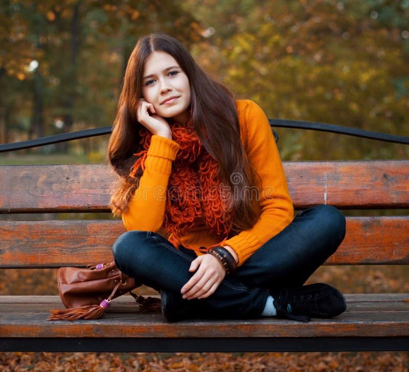 Muchacha en banco en parque del otoño fotografía de archivo