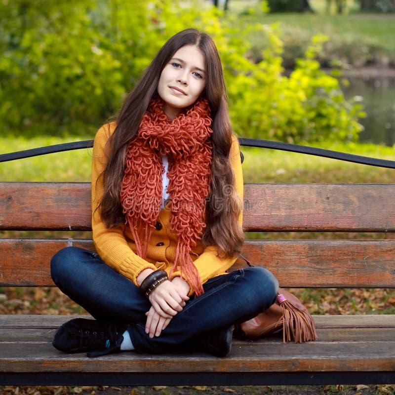 Muchacha en banco en parque del otoño foto de archivo