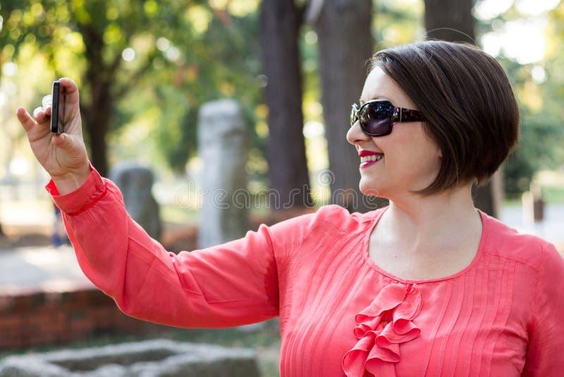 Muchacha en blusa rosada que sonríe y que toma Selfie en un parque fotografía de archivo