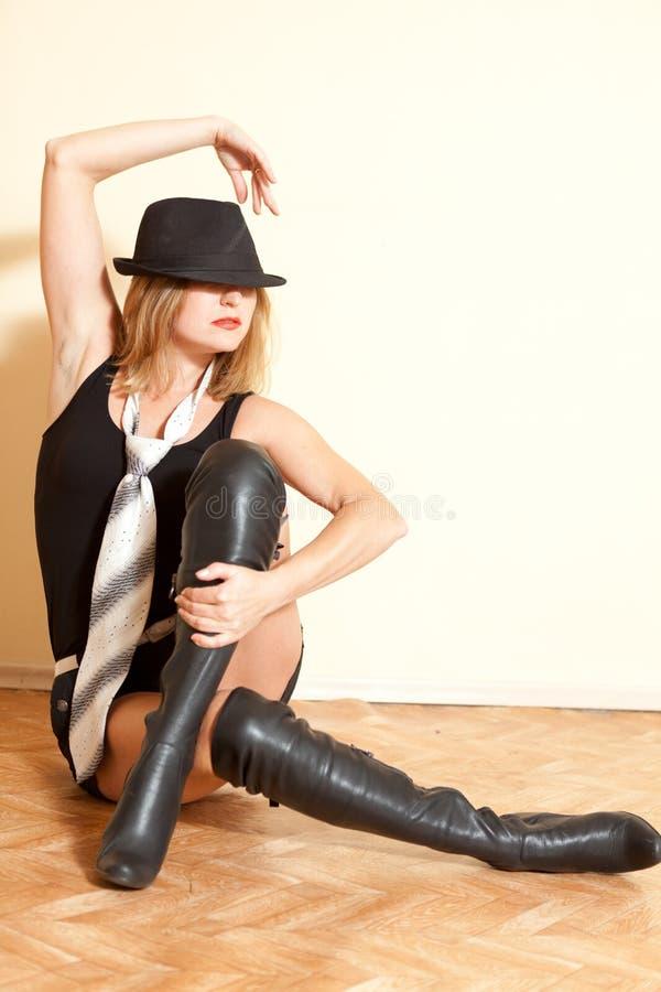 Muchacha en botas del enchufe y sombrero que presenta en interior del fondo fotografía de archivo