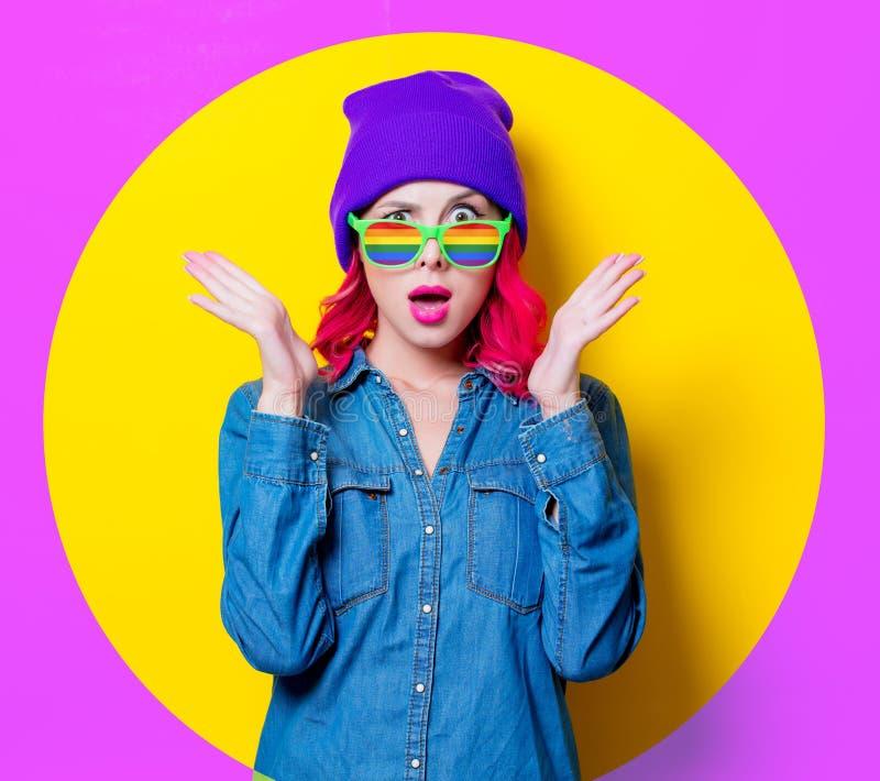 Muchacha en camisa azul, sombrero púrpura y vidrios del arco iris imágenes de archivo libres de regalías