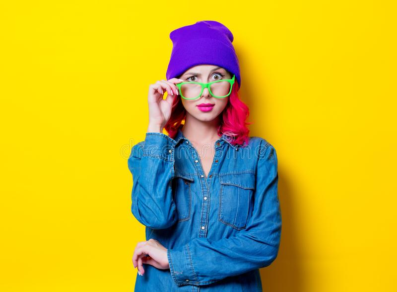 Muchacha en camisa azul, sombrero púrpura y vidrios verdes fotografía de archivo
