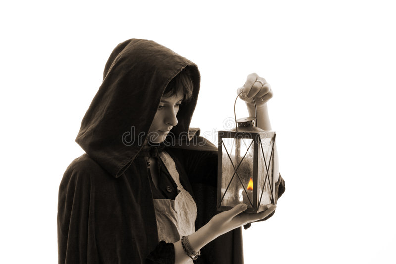 Muchacha en capote con una vela-linterna fotografía de archivo libre de regalías