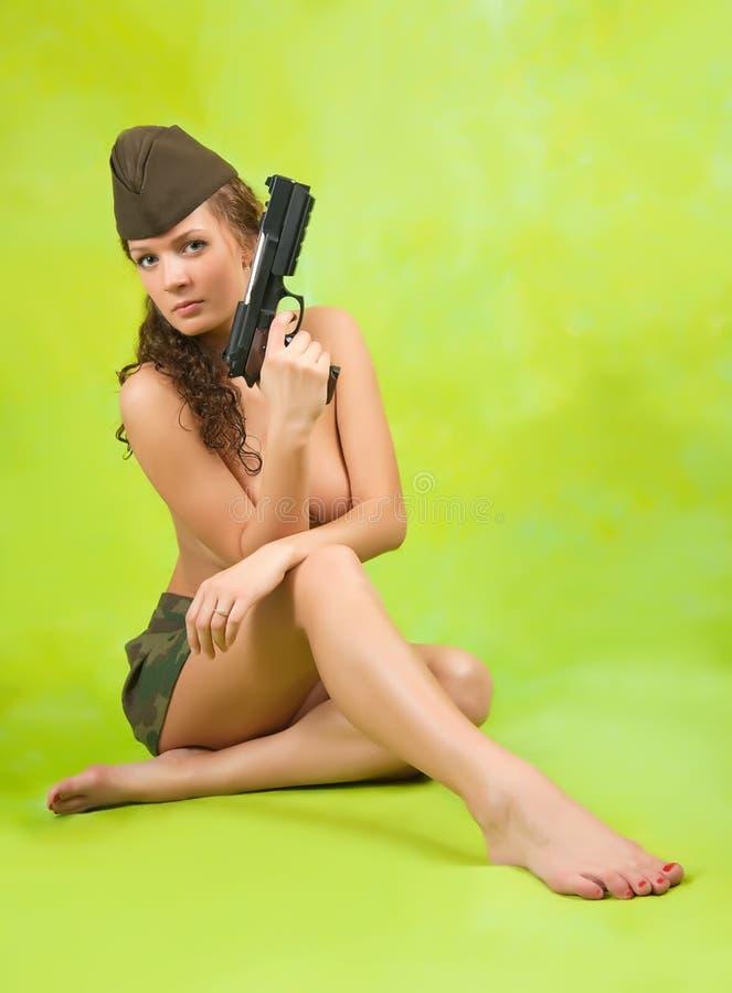 Muchacha en casquillo de guarnición con el arma foto de archivo libre de regalías