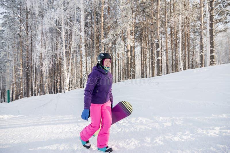 Muchacha en chaqueta púrpura y pantalones rosados con la snowboard en las manos foto de archivo