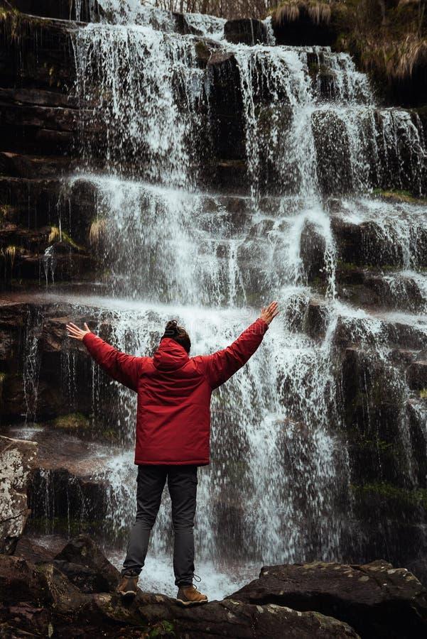 Muchacha en chaqueta roja por la cascada imagenes de archivo