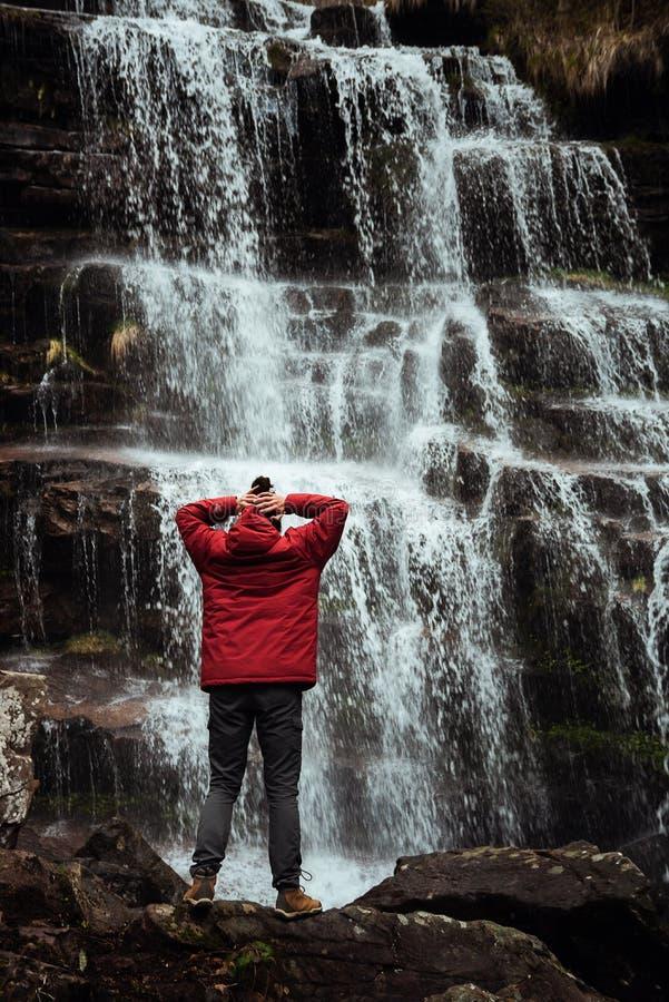Muchacha en chaqueta roja por la cascada imagen de archivo