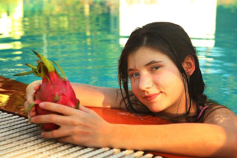 Muchacha en cierre de la piscina encima del retrato con la fruta del dragón foto de archivo