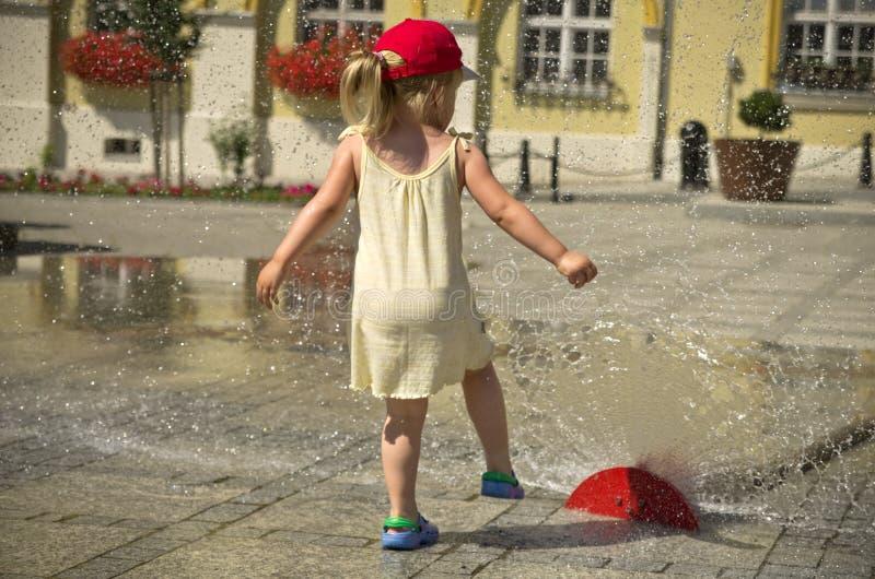 Muchacha en ciudad caliente del verano con la regadera del agua imagen de archivo