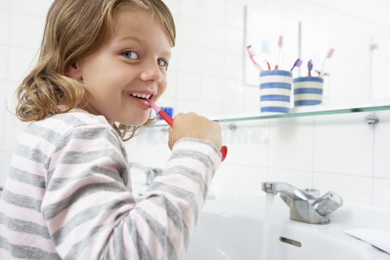 Muchacha en dientes de cepillado del cuarto de baño imagen de archivo