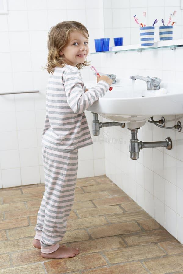 Muchacha en dientes de cepillado del cuarto de baño imagen de archivo libre de regalías