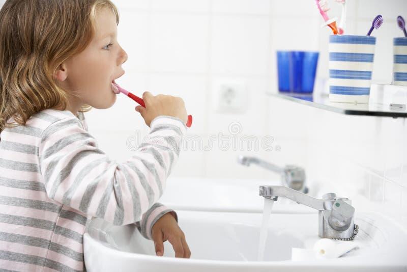 Muchacha en dientes de cepillado del cuarto de baño fotografía de archivo libre de regalías