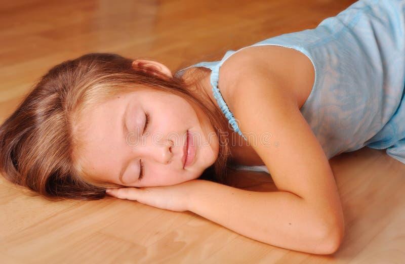 Muchacha en dormir azul, mintiendo en el suelo fotografía de archivo