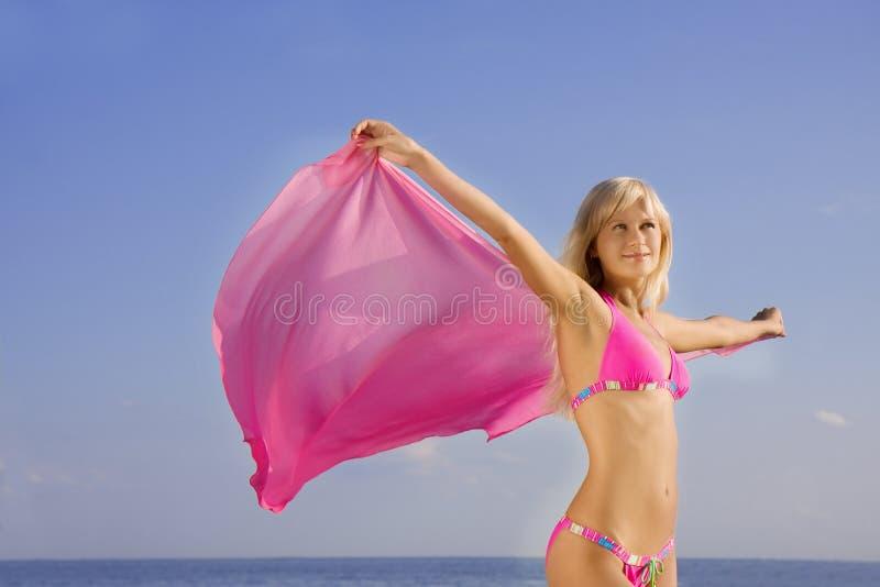 Muchacha en el bañador rosado en la playa foto de archivo