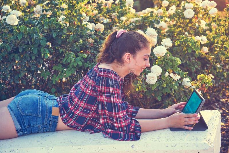 Muchacha en el banco de parque que juega con la tableta fotografía de archivo