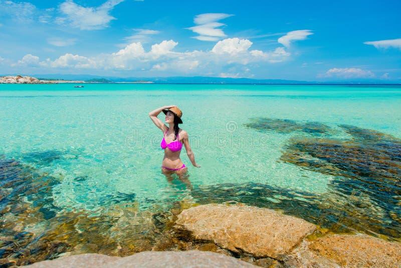 Muchacha en el bikini rosado que se coloca en un agua en la playa imagen de archivo