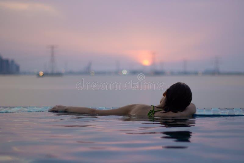 Muchacha en el borde de la piscina del infinito fotos de archivo