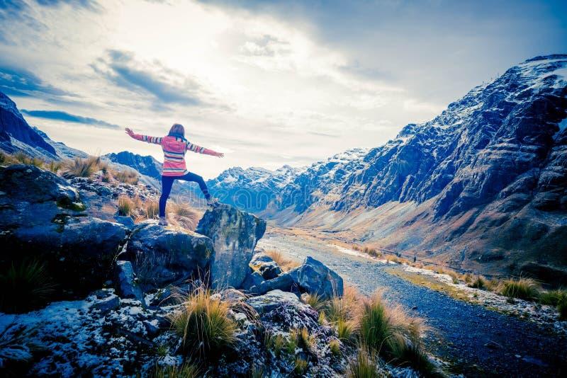 Muchacha en el borde de la roca que toma el placer del paisaje de los Andes imagen de archivo libre de regalías