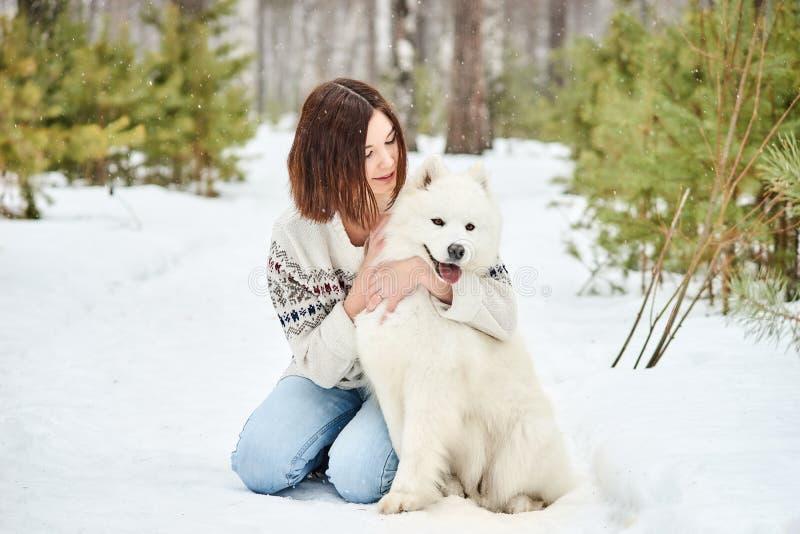 Muchacha en el bosque del invierno que camina con un perro La nieve está cayendo fotografía de archivo libre de regalías