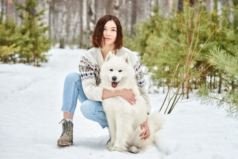 Muchacha en el bosque del invierno que camina con un perro La nieve está cayendo imagen de archivo libre de regalías