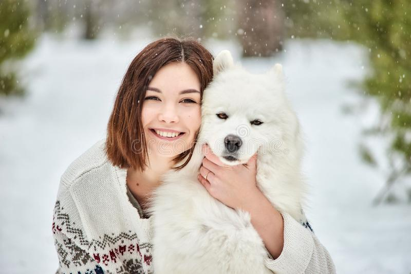 Muchacha en el bosque del invierno que camina con un perro La nieve está cayendo imágenes de archivo libres de regalías