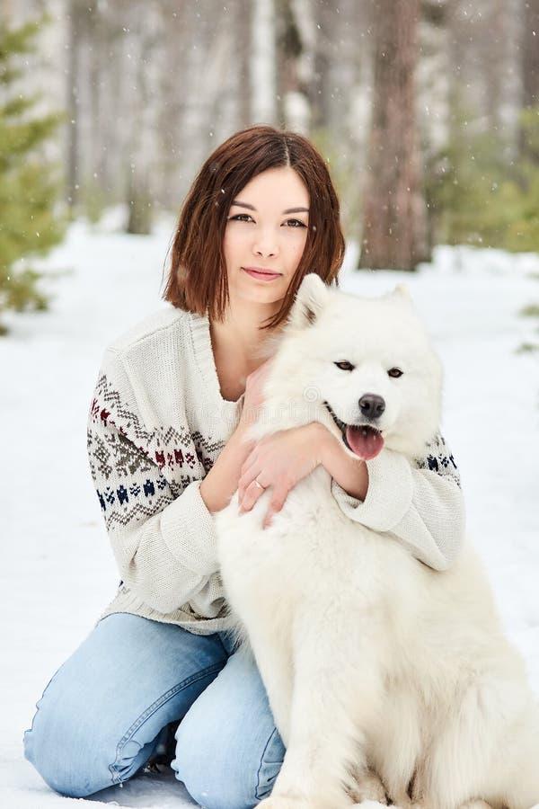 Muchacha en el bosque del invierno que camina con un perro La nieve está cayendo imagenes de archivo