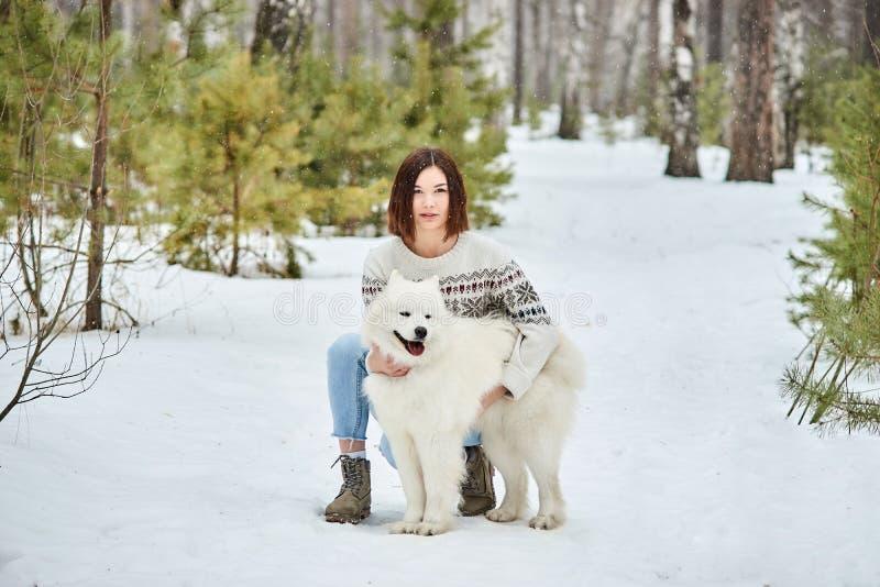 Muchacha en el bosque del invierno que camina con un perro La nieve está cayendo foto de archivo