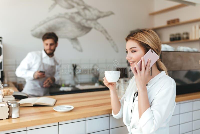 Muchacha en el café de consumición del contador y el hablar en barista del rato del teléfono móvil usando su teléfono foto de archivo