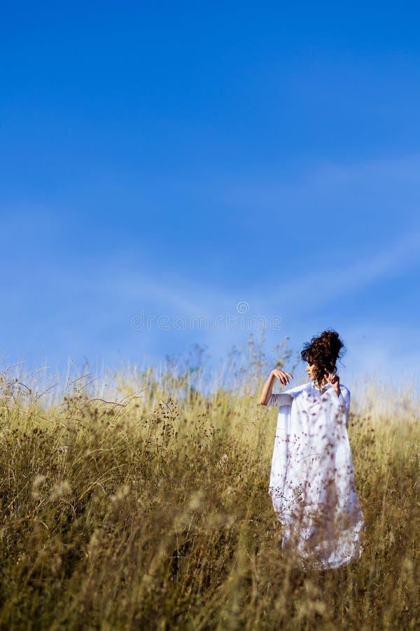 Muchacha en el campo con el cielo azul fotografía de archivo