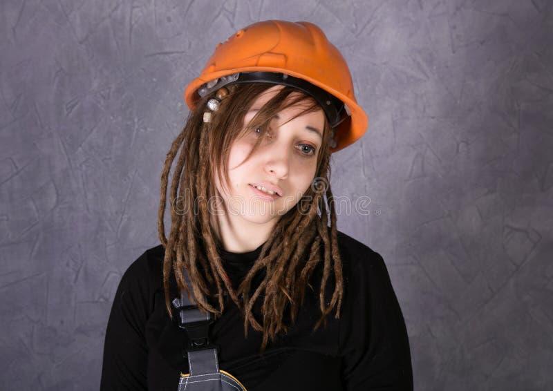 Muchacha en el chaleco anaranjado del casco de seguridad que sostiene la herramienta del martillo fotos de archivo libres de regalías