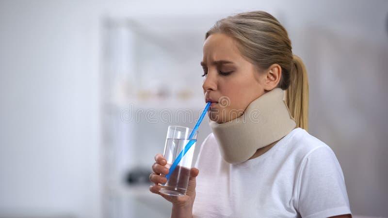 Muchacha en el cuello cervical de la espuma que intenta beber el agua de cristal con tentativa pobre de la paja foto de archivo libre de regalías