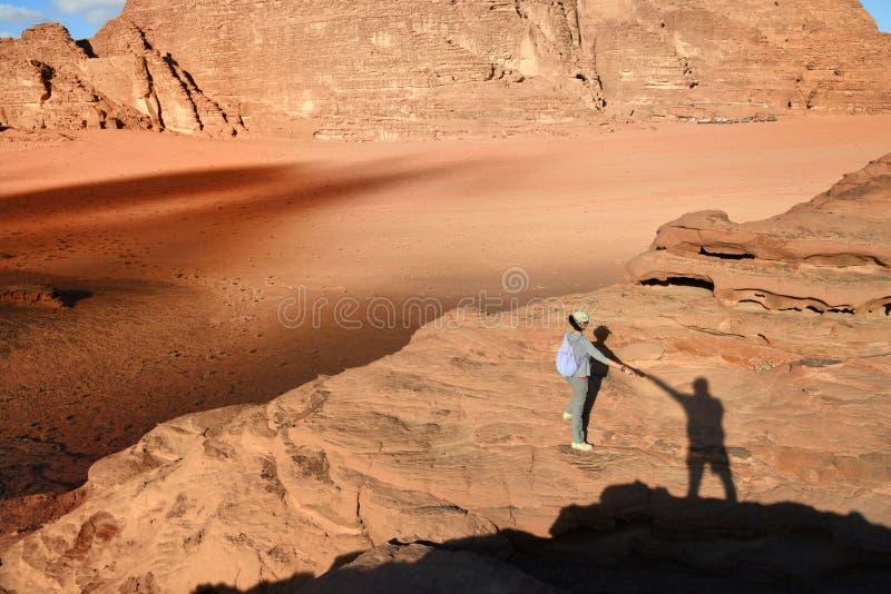 Muchacha en el desierto Wadi Rum durante puesta del sol imágenes de archivo libres de regalías