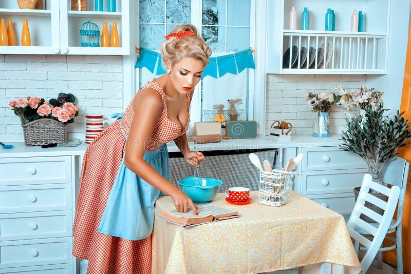 Muchacha en el libro de la receta de la lectura de la cocina fotos de archivo