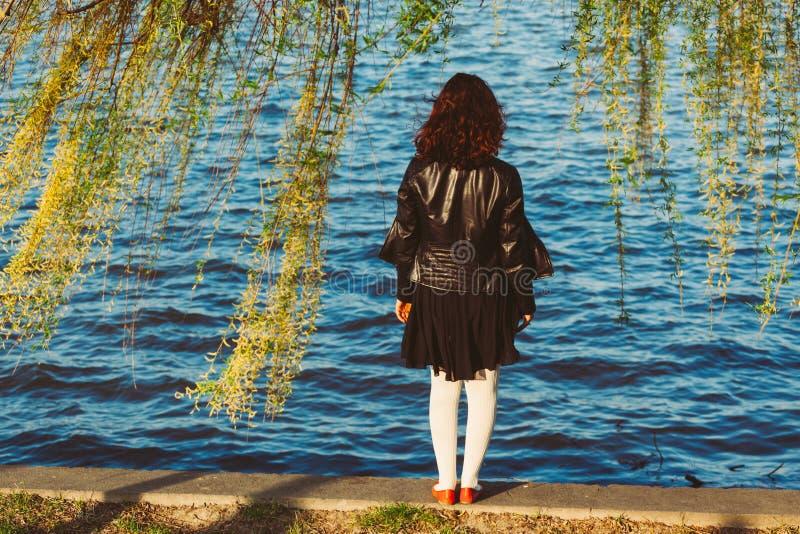 Muchacha en el parque, mirando el río fotografía de archivo libre de regalías