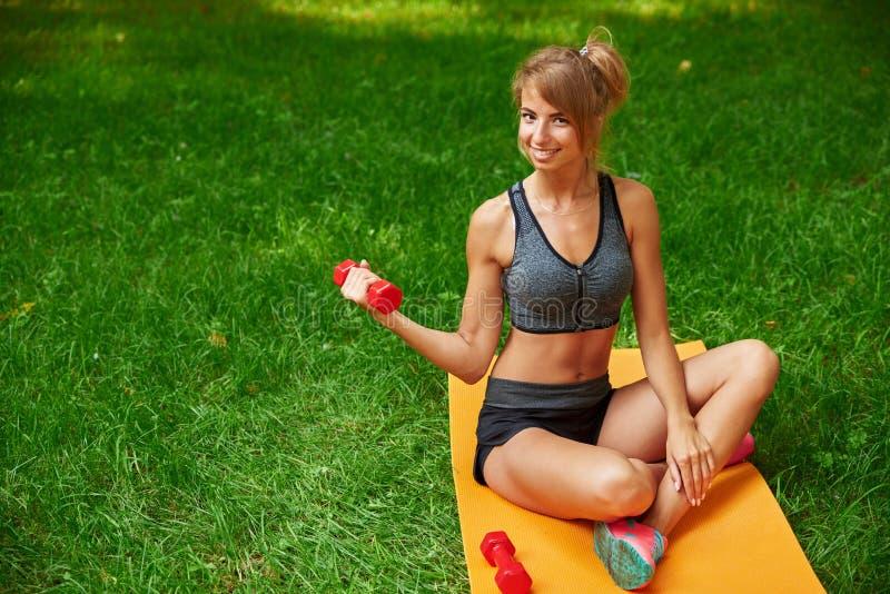 Muchacha en el parque y contratada a diversos ejercicios con pesa de gimnasia y la estera imagenes de archivo