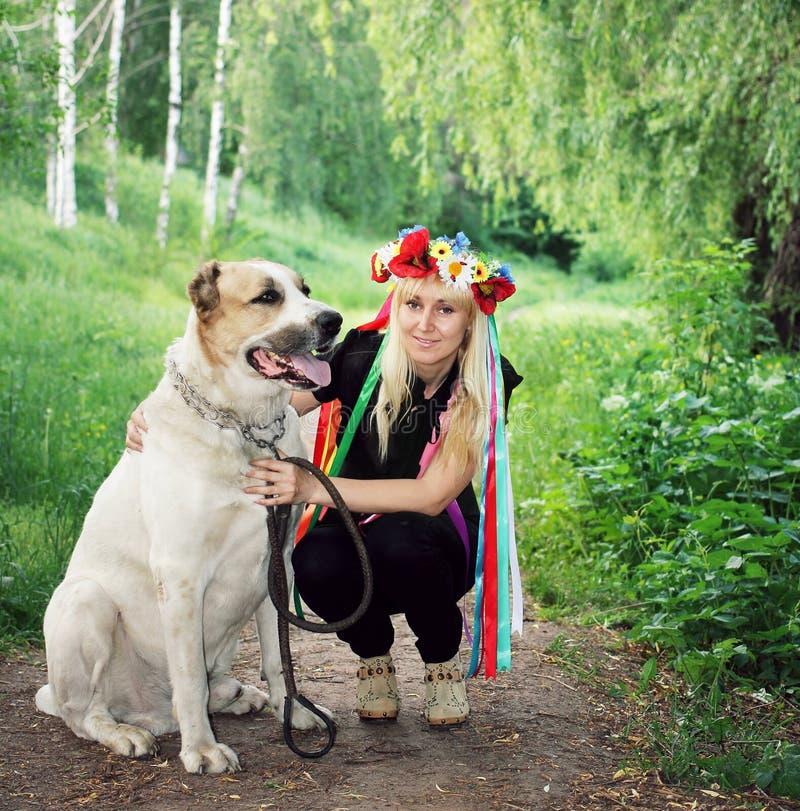 Muchacha en el perro grande siguiente de la guirnalda nacional foto de archivo