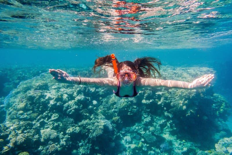 Muchacha en el salto de la máscara de la natación en el Mar Rojo cerca del arrecife de coral fotos de archivo