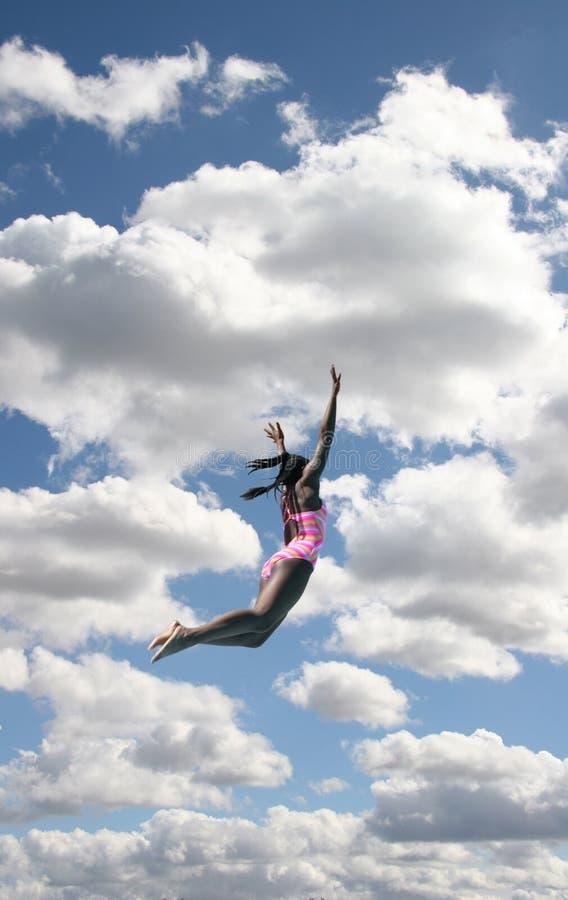 Muchacha en el salto del traje de baño en cielo imagen de archivo libre de regalías