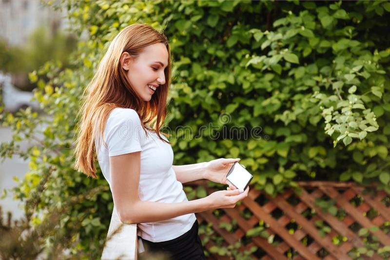 Muchacha en el smartphone del iwith del parque fotografía de archivo