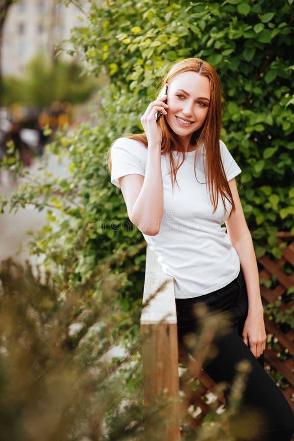 Muchacha en el smartphone del iwith del parque imagen de archivo libre de regalías