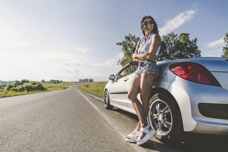 Muchacha en el sol brillante en el camino con el coche del cabriolé El concepto de aventura y de viaje solamente Viajes por carre fotos de archivo