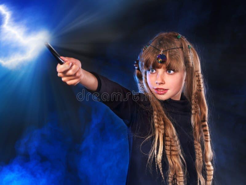 Muchacha en el sombrero de la bruja con la varita mágica. fotografía de archivo libre de regalías