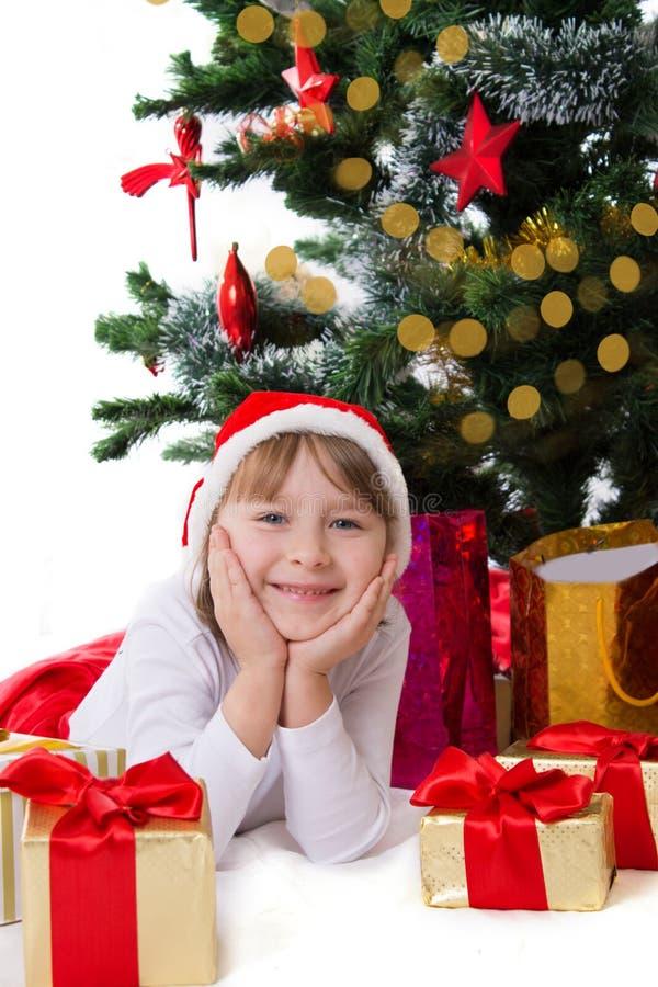 Muchacha en el sombrero de Papá Noel que miente debajo del árbol de navidad foto de archivo libre de regalías