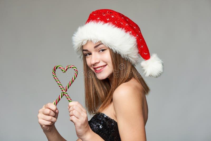 Muchacha en el sombrero de Papá Noel que sostiene los caramelos de la Navidad en forma del corazón imagenes de archivo
