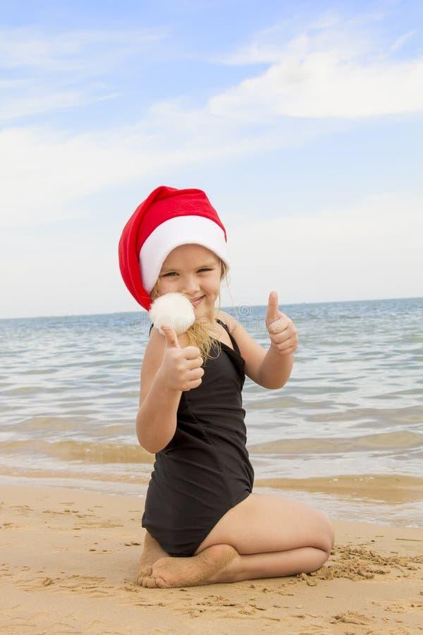 Muchacha en el sombrero de santa en la playa imagenes de archivo
