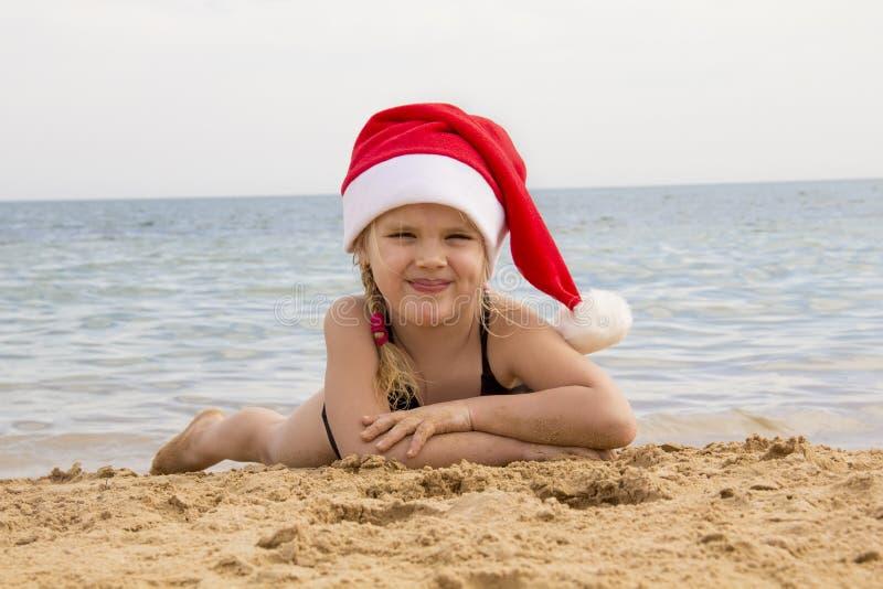 Muchacha en el sombrero de santa en la playa imágenes de archivo libres de regalías