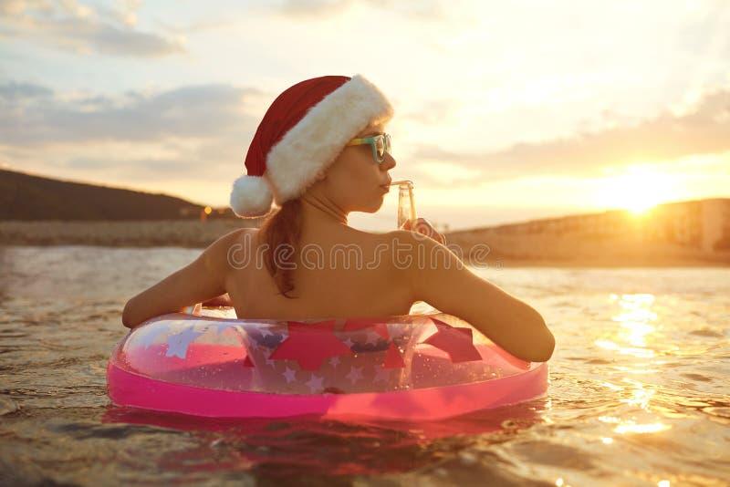 Muchacha en el sombrero de santa en la playa por el mar el día de la Navidad fotografía de archivo libre de regalías