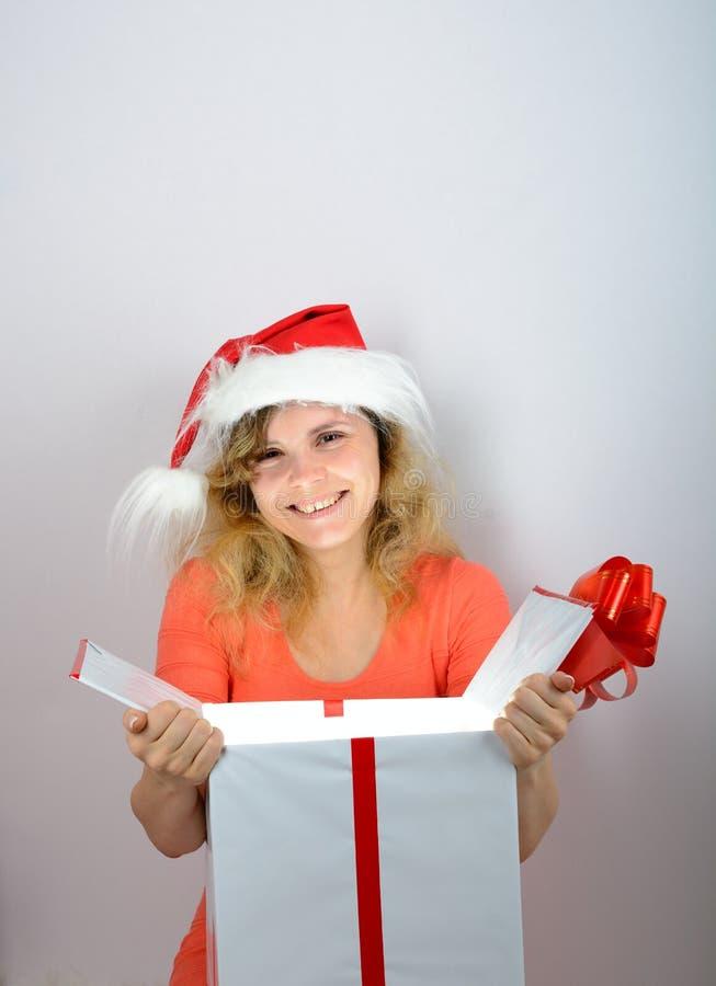 Muchacha en el sombrero de santa que abre una caja fotografía de archivo libre de regalías